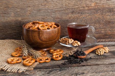 Tea in a cup, nuts and cracker on a wooden background