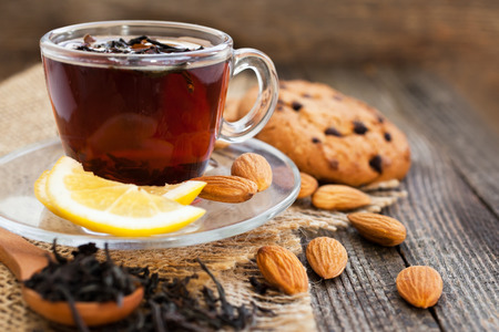 Tea in a cup with lemon and nuts closeup