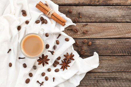 Coffee in a cup with spices and white cloth on a wooden background Reklamní fotografie - 93640679