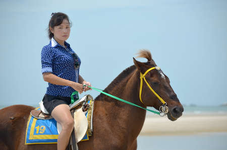 A woman with horse on the Beach