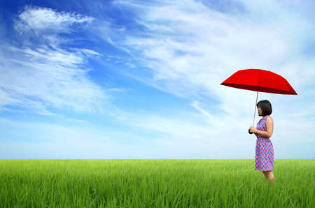 young woman with red umbrella in a green field photo