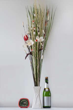 spuria: fiori finti con bottiglia di vino e sveglia rossa Archivio Fotografico