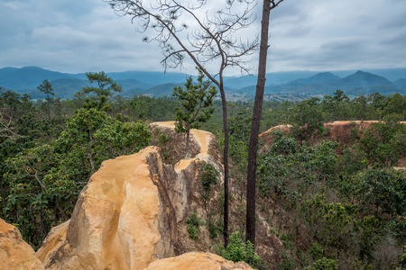 The cliff of orange soil mountain in the forest with cloudy sky view, Traveling in Thailand Stock Photo