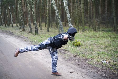 a lonely S.W.A.T ranger in the forest standing on one leg photo
