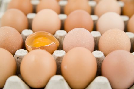 plenty of eggs in paper container. One egg is opened Standard-Bild
