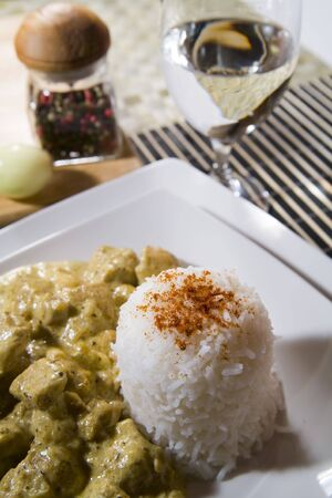 chicken in curry spice with rice and wine photo