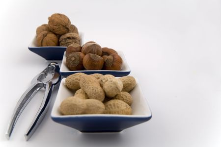 walnuts, hazelnuts and peanuts in three bowls on white background photo