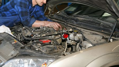 mechanic working with engine in the car service photo