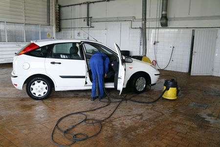 cleaning service: man cleaning a car in the car service