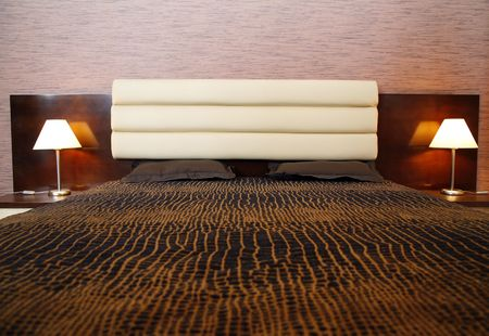 comfortable bed and two lamps photo
