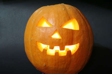 wacky: face of halloween pumpkin on black background with candle inside Stock Photo