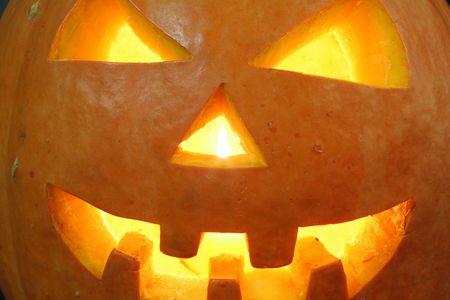 jackolantern: face of halloween pumpkin on black background with candle inside Stock Photo