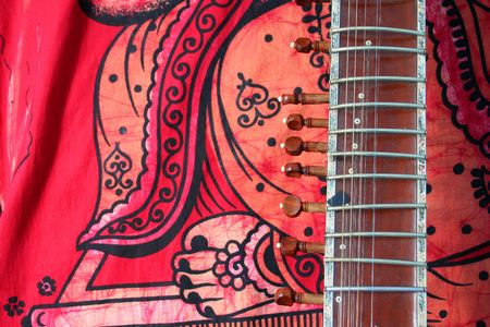 old sitar on red background - ancient indian instrument