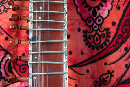 ancient yoga: old sitar on red background - ancient indian instrument