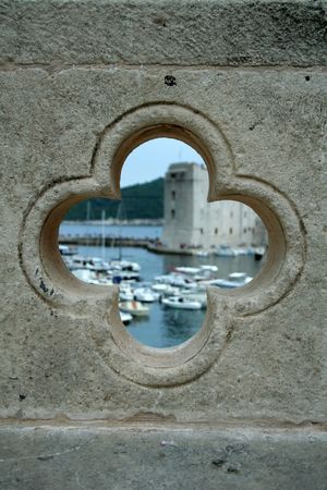 view on the port in Dubrovnik from the hole in bridge - the wall is sharp and the port is blurred photo