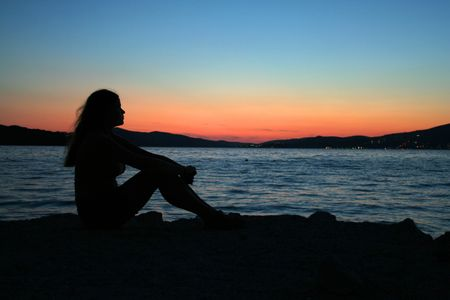 Sexy Frau sitzt am Strand bei Sonnenuntergang  Standard-Bild - 764361