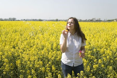 childchood: woman blowing bubbles over the rape field
