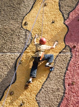 imitation: boy climbing the wall - imitation of real rock