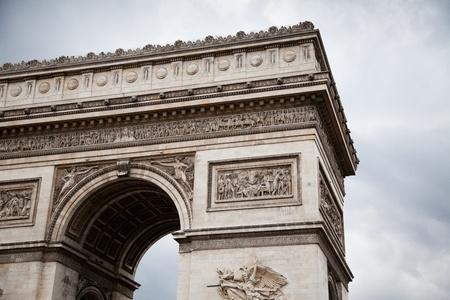 Arc de Triomphe (Arch of Triumph) on gloomy sky background photo