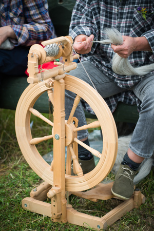 spinning wheel: woman working with spinning wheel Stock Photo