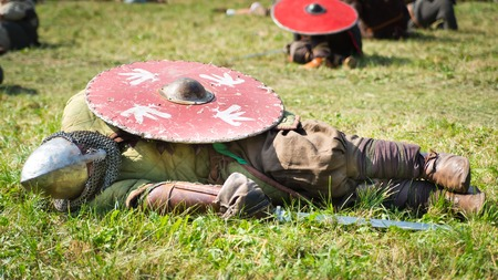 defeated: Defeated warrior lying on the grass with his shield