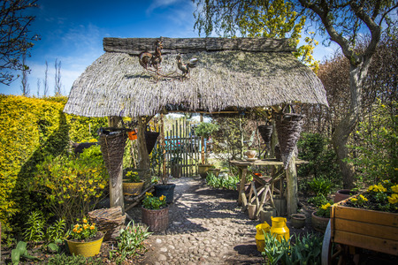 wicket gate: Old gazebo with thatched roof surrounded by plants Stock Photo