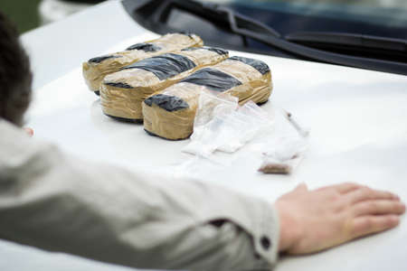 Detained criminal on the hood of a car with packets of drugs. Drugs, the fight against drug addiction.