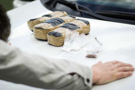 Vastgehouden crimineel op de motorkap van een auto met pakjes drugs. Drugs, de strijd tegen drugsverslaving.