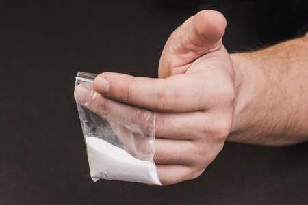 criminal: Addict holding drug bag in his hand on a black background.