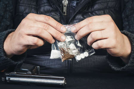 criminal: Young man sitting at the table with arms holding packages with drugs. Drug addiction, crime. Stock Photo