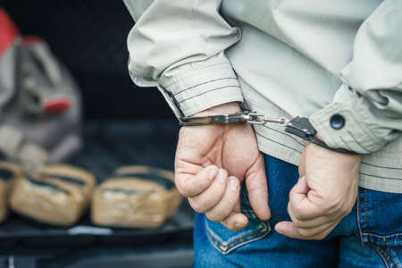 criminal: A man in handcuffs detained the transportation of drugs.