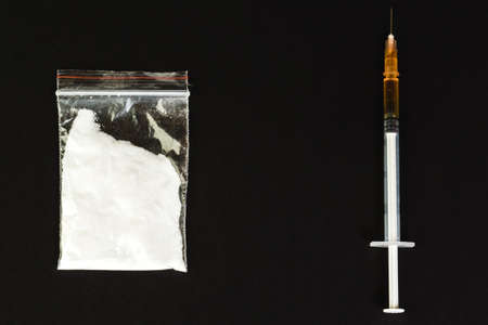 criminal: Syringe with drug and cooked heroin. Cocaine in the package. Isolated on a black background.