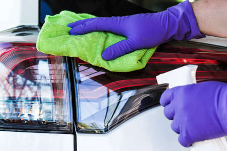 Male hand wearing rubber gloves microfiber wipes and polishes the car. Car wash.