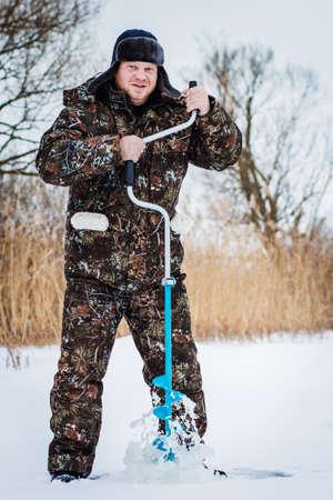 Ice fisherman drill on winter lake Stock Photo