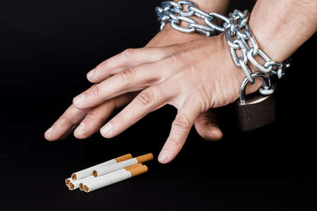 Cigarettes and hand of a man tangled in chains . The concept of nicotine addiction. Isolated on black background.