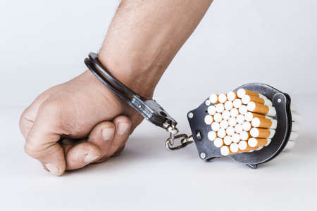 Cigarettes and hand of a man in handcuffs. The concept of nicotine addiction, a bad habit. Isolated on a white background.