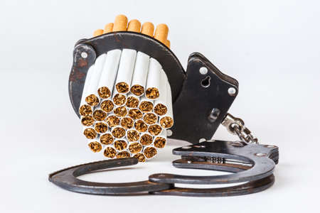 Cigarettes and handcuffs, the concept of nicotine addiction. Isolated on a white background.