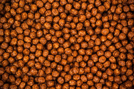 Chocolate breakfast cereal texture. Cereal balls as background. Chocolate corn balls .