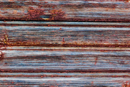 Red board wall of an old barn. Textured and flaking red paint from old farm building.