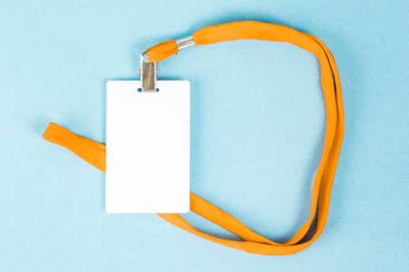 Tarjeta de identificación vacía / icono con una correa naranja, sobre un fondo azul. Espacio para texto Foto de archivo - 91214973