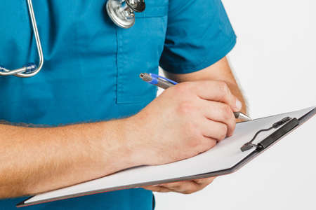 Male doctor with stethoscope writing on clipboard message or board, on white background Stock Photo