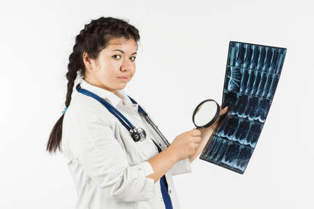 Young female doctor looking at x-ray image. On a white background