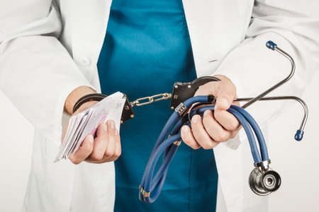 Doctor with a stethoscope and euro-banknotes and handcuffs. Crime