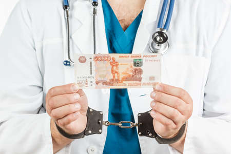 Doctor with a stethoscope and 5000 banknotes and handcuffs. a crime. on a white background. Stock Photo