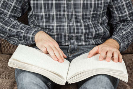 El ciego estaba leyendo un libro escrito en Braille. Toca con tu dedo el código de braille. Un libro con texto en Braille. Foto de archivo - 91207624