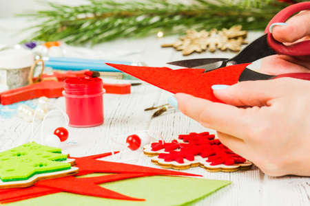 Christmas decorations, balls, toys and gift boxes on an old wooden board. Female hands carve a Christmas tree.