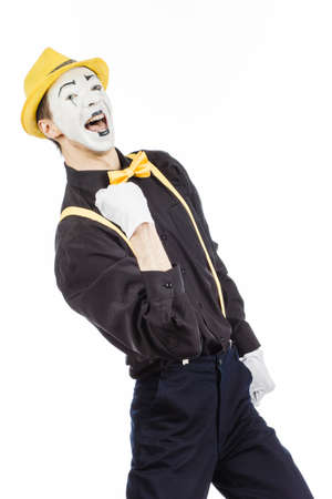 A happy young man, an actor, pantomime, rejoices in success. On a white background. Imagens