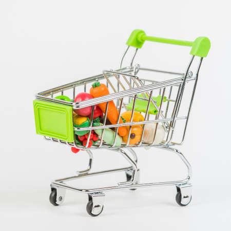 Toy miniature shopping trolley with an assortment of colorful oversized fruits and vegetables