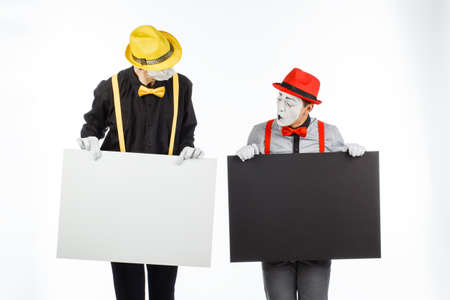 Two funny mimes holding a white blank on a white background.
