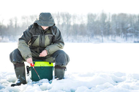 A young man is fishing from a hole on ice. Winter fishing. Stock Photo